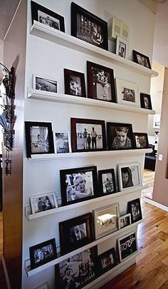 Photo Gallery Idea   Moulding strips attached horizontally to a wall of the same color. Use the strips as a ledge on which to sit photos. This makes it easy to add new & remove old photos.