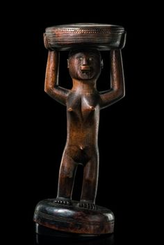"""Makonde wood, brown patina, blackened in parts, in shape of a standing female figure with lip plug and inset glass eyes, a round seat with ornamented rim, min. dam., fissures, traces of insect caused damage, slight traces of abrasion, on base; the general denomination for this disc was """"pelele"""". The largest discs were only allowed for women who had given birth to at least seven children.  H: 37,5 cm"""