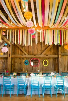 lovely colorful wedding reception decor with teal, yellow, red, green, pink and blue streamers hung over rafters