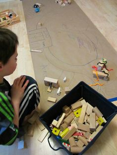 Neem een stuk behang en laat de kinderen er een dierentuin op tekenen. Met plastic dieren en blokken maak je het compleet