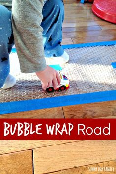 Make a road with bubble wrap and tape! Truck loving toddlers will have hours of fun popping along this super easy road - a perfect indoor activity for toddlers!
