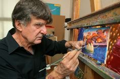 Artist John Asaro works in studio on a small painting of sea mammals ...