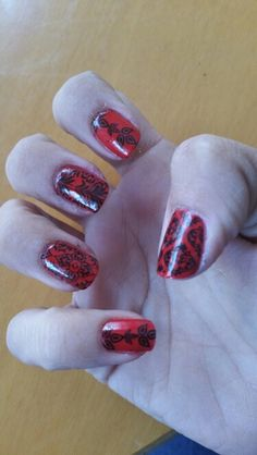 Uñas color roja con estampado arabesco negro.