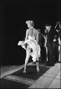 "Marilyn Monroe in NYC, with director Billy Wilder in the background, during the filming of ""The Seven Year Itch."" (1954)"