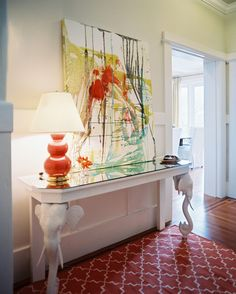Hallway - An orange lamp and patterned rug balanced by a white elephant-motif console table