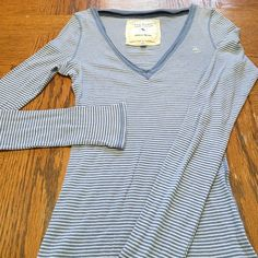 Abercrombie comfy long sleeve shirt Very cute and comfy long sleeve Abercrombie striped shirt. V neck and is light blue and white striped. One tiny hole on sleeve but can't even see when wearing or looking real close to that spot. Shown on last picture. Abercrombie & Fitch Tops Tees - Long Sleeve