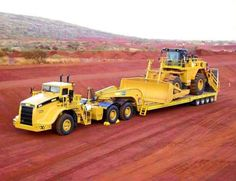 Guns, Oil, & Dirt Haul Maxx with a Cat wheel dozer on the wagon