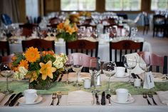 Wedding reception table decorated with a green table runner and orange flowers