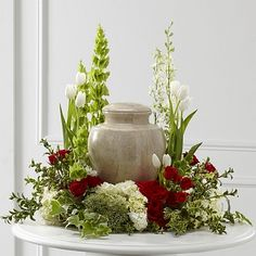 The FTD® tears of comfort™ arrangement - n elegant and sophisticated way to surround their urn with floral beauty at the final farewell service - Rich red roses and spray roses are vivid and bright arranged amongst white tulips, larkspur, hydrangea, and trachelium, accented with the bright greens of Bells of Ireland, hypericum berries, ivy and myrtle