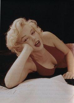 Marilyn Monroe. Red dress sitting. Photo by Milton Greene, 1957.