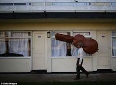 The double bass player from The Zazou Cowboys carries his instrument back to his chalet Vintage Festival, Holiday Park, Double Bass, East Sussex, Orchestra, Celebrities, Face, Rockabilly Cars, Cowboys