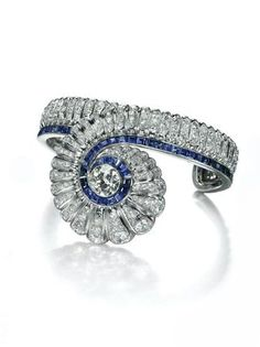 A Sapphire and Diamond Bangle, by Suzanne Belperron. The central scalloped swirl centering upon a circular-cut diamond collet and extending a rigid cuff, set with diamonds and enhanced by a line of calibré-cut sapphires, 1941-1945. Christie's. Jewels for Hope: The Collection of Mrs Lily Safra .
