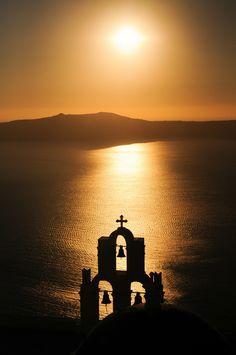 Anastasi (Resurrection) Church silhouetted against the setting sun in Imerovigli, Santorini, Greece.