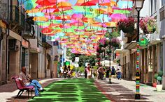 In Águeda, a small Portuguese town, some streets are decorated with colorful umbrellas. The umbrellas look like they're magically floating in mid-air, making people walking on the street without the hot summer sun on their heads!    Photo by Patrícia Almeida.