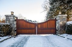 Mahogany double-swing automated driveway gates with tall stone pillars. Scallop curved top, tongue-and-groove construction, and transitional style design. Tri State Gate - Bedford HIlls, NY | 914-244-0018 | tristategate.com