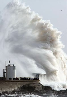 Image: Porthcawl, Bridgend, South Wales, 8th Feb 2014   People look on as high waves strike the harbour wall at Porthcawl, south Wales - There's a lighthouse under that wave!