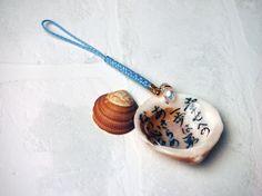 【南三陸町 泊貝っこ(とまりげっこ)の貝キーホルダー】天然貝のストラップです。貝の内側に、それぞれ書によるメッセージが書いてあります。(サイズ 貝 約4cm 紐 7cm)ストラップと一緒に、南三陸町でしかとれない泊貝っこ(とまりげっこ)が1枚入っています。それぞれ¥600。