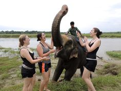 """Bathing with Elephants"" By: Elizabeth McBride. Caption: ""Three engineering students bathe with an elephant in Nepal after volunteering in India with SWE Overseas."" Category: Wolverines Abroad. Program: SWE Overseas in India"