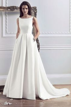 modern plain bateau neckline wedding dress with a pleated skirt and pockets