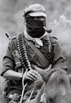 """deathriders: """" fyeah-history: """" Subcomandante Marcos, the spokesman of the Zapatista Army of National Liberation, smoking a pipe atop a horse in Chiapas Subcomandante Marcos is the spokesperson for. Mexican Revolution, Post Apocalyptic Fashion, By Any Means Necessary, Smoke, Black And White, Pipe Smoking, Men Smoking, Cigar Smoking, People"""