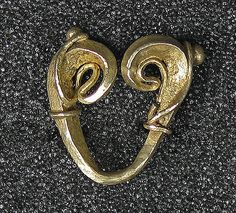 One of two double scroll fertility earrings, gold. Central Java, 8th-12th century