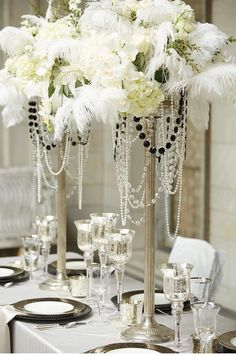 Tall white floral centerpiece with feathers and pearls