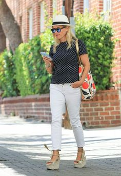 Reese Witherspoon wears a polka dot t-shirt, cropped white jeans, espadrilles, mirrored sunglasses
