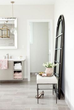 Incredible bathroom with floating gray lacquered vanity with towel shelves, filled with white and pink towels finished with a white quartz counter which frames an undermount sink with modern faucet situated below a beveled vanity mirror which reflects a brass arch top lantern lit by a glass sphere pendant light.