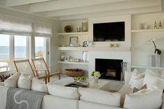 A comfortable white sectional is paired with contemporary armchairs and sleek white coffee table to create a relaxed living room for this Martha's Vineyard home. Exposed white ceiling beams add architectural details, while built-in shelving houses the TV, fireplace and pretty accessories.