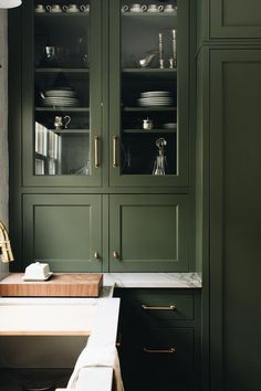 Gray shaker cabinets donning oval brass knobs are fixed against a gray marble countertop and stacked beneath glass front cabinets fitted with brass pulls.