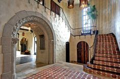 The two-story entry sets a dramatic tone with its stone arch, wrought-iron stair rails and floor inlays.