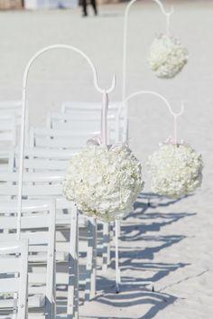 hydrangea poms aisle decor for beach wedding ceremony / Koru Wedding Style: {Pink & White Florida Beach Wedding} Laura & Stephen