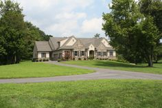 Custom home with stone veneer, board and batten shutters, and a 3-car garage.