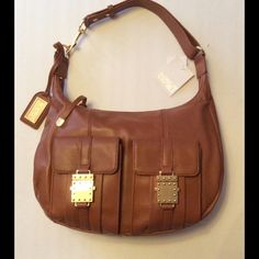 "Badgley Mischka Brown Leather Handbag NWT Authentic Badgley Mischka Leather Handbag. Lucia Nappa , Cognac. Brown/Gold-Tone Hardware. 1 inside zipper pocket, 2 inside slip pockets. 2 outside compartments 7"" x 5"". Adjustable Straps. Measurement 13"" x 9"". Includes Hangtag and Dustbag. This bag in brand new, tags still attached. Gorgeous.  No Trades No Golds  Badgley Mischka Bags"