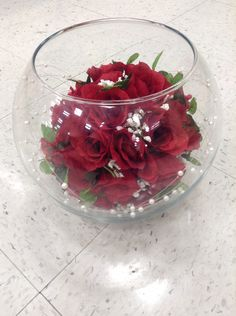 Red rose bouquet in fish bowl with white sand and pearl strands arrangement