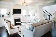 transitional living room interior design by Kerry Spears Interiors featuring an open living room, blue accents, transitional decor, gallery wall and french wingback chairs.
