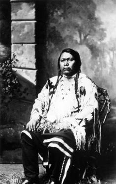"1880 Sitting portrait of Ouray, Native American Ute leader. He wears braids, a fringed buckskin shirt, leggings, and boots. The image was taken during the Utes' last treaty negotiations at Washington, D. C., only months before Ouray's death.  ""The Ute shirt, worn by Ouray in this and other 1880 photographs was presented by his wife, Chipeta, to Secretary of the Interior Carl Schurz, after Ouray's death in August 1880 and is now in the Heve Museum of the American Indian, New York City."""