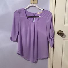 """Lilac spring blouse  ‼️‼️ALL FUNDS FOING TOWARDS A MISSION TRIP TO GERMANY I AM TAKING IN JUNE 2016‼️‼️Lilac colored Spring/Summer blouse from a local boutique! EUC. 3/4 sleeves. Cute button on the draped sleeves. Brand is """"fresh tart"""". Semi-sheer. Not sheer enough for a full camisole underneath, but it is sheer enough to wear a bandeau  Size SMALL. 100% poly. Washed only according to care tag. NO TRADES. boutique Tops Blouses"""