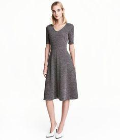 Svart/Vit mönstrad. En knälång klänning i strukturvävd kvalitet. Klänningen är v-ringad och har kort ärm. Avskuren i midjan och lätt utställd nedtill. Dold