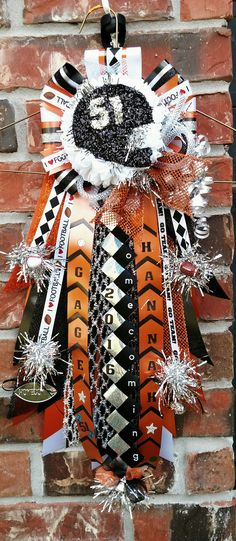 "Boys 18"" garter mum. Orange black white and silver homecoming mum. Designed by Crafty bug"