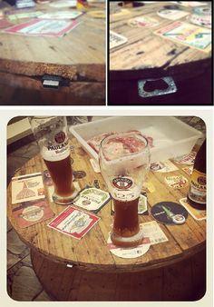 Mesa feita de carretel de fibra ótica, com acessórios geniais: abridor de garrafa e  portinha USB. Para decorar, selos de cervejas.