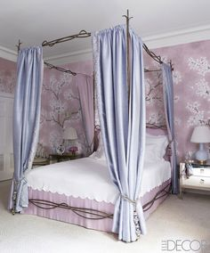 The master bedroom's cast-metal bed is a custom design, the headboard and bed skirt are of a fabric by Lelievre, and the canopy curtains are of a silk by Dedar that was embroidered by Penn & Fletcher and lined with a fabric by Stark; the mirrored bedside tables are from R.E. Steele Antiques, the lamps are by Christopher Spitzmiller, and the custom-color wallpaper is by Gracie.