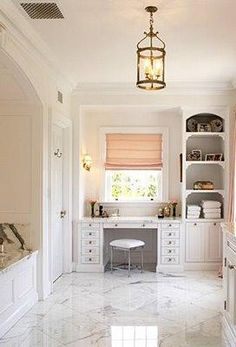 Windsor Smith Home Lovely chic white gray pink bathroom design with white carrara marble fllors and counter tops, brass lantern pendant light, chrome stool, white vanity built-in desk cabinets shelves, silk pink roman shade and drapes. white gray pink bathroom colors.