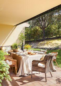 Comedor exterior en porche con sillas de fibra natural, mantel beige, vajilla y plantas