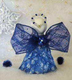 Zafiro es un adorno hermoso ángel azul zafiro. Su cuerpo está hecho de una tela azul con remolinos de copo de nieve metálicas y alas son una cinta brillante brillo azul. Su halo es moldeado para ajustarse a mano. Ella es una hermosa adición a su colección de adorno o decoración de la Navidad!  Todo lo necesario para hacer Zafiro está incluido excepto los pernos rectos. Usted necesitará alrededor de 250 pines. Me recomendó 1 y 1 1/16 funcionará también.