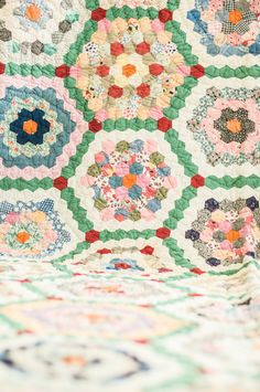 Love the green with red border around each flower. Antique Quilt - 'grandmother's flower garden'. via Etsy.
