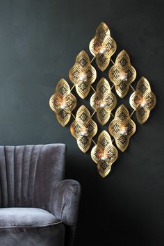 The wall mounted Kasba tea light holder is a super eye-catching piece for the home Created in lazer cut gold coloured metal the waves of design each