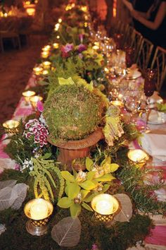 Forest-green mosses nestle among colorful Sweet William flowers and luxe green orchids. Antique votives add charm.Photo Credit: Philippe Cheng