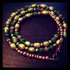"""22"""" necklace, made with olive green freshwater rice pearls, dark green dyed quartzite, copper metal findings and copper seed beads, with a lobster claw closure."""
