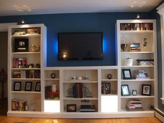 Simple and clever transformation of the IKEA BILLY bookshelves by modifing and adding trim and lighting. Get a custom look for the living room. Get the directions